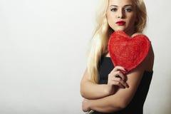 Reizende schöne blonde Frau mit rotem Herzen. Schönheits-Mädchen. Zeigen Sie Liebes-Symbol. Valentinstag. Schwarzes Kleid Stockfoto