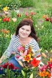 Reizende schöne Frau mit Lilienblumenstrauß in den Händen stockfotografie