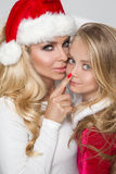 Reizende sexy blonde Mutter mit einer Babytochter gekleidet als Santa Claus Lizenzfreie Stockfotos
