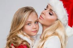 Reizende sexy blonde Mutter mit einer Babytochter gekleidet als Santa Claus Lizenzfreie Stockbilder