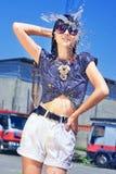 Reizende sexy nasse Frau, Wassertropfen, Hände oben, kurze kurze Hosen, schwarzes langes Haar und Gläser in den Hintergrund-LKWs Lizenzfreies Stockbild
