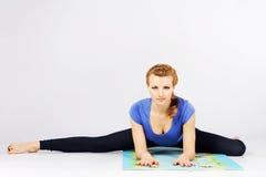Reizende sportliche Frau, die Übung ausdehnend tut Lizenzfreie Stockfotos