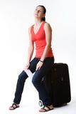 Träumerische Frau, die auf einem Koffer sitzt Stockfoto