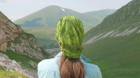 Reizende vrouw op berg en groene valleiachtergrond Wandeling en het beklimmen stock videobeelden