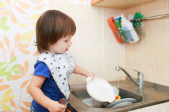 Reizende waschende Teller des kleinen Jungen Stockbilder