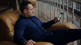 Reizende zakenman die bij zitkamer met smartphone en bagage wachten stock footage
