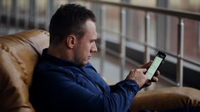 Reizende zakenman die bij zitkamer met smartphone en bagage wachten stock videobeelden