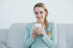 Reizende zufällige Frau, die eine Schale sitzt auf Couch hält stockfotografie