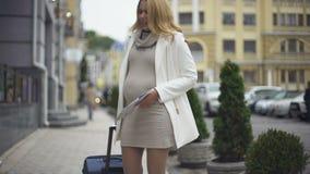Reizende zwangere dame met koffer en kaart die buikpijn op stadsstraat voelen stock footage
