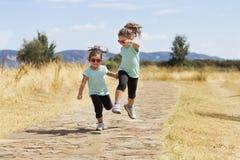 Reizende Zwillinge, die entlang Weg in der Landschaft springen Lizenzfreies Stockfoto