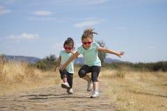 Reizende Zwillinge, die entlang Weg in der Landschaft springen Lizenzfreie Stockfotos