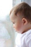 Reizender Babyblick aus Fenster heraus Lizenzfreie Stockfotos