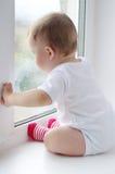 Reizender Babyblick aus Fenster im regnerischen Wetter heraus Lizenzfreie Stockbilder