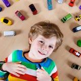 Reizender blonder Kinderjunge, der mit vielen Spielzeugautos Innen spielt Lizenzfreie Stockbilder