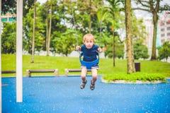 Reizender blonder kleiner Junge auf einem Schwingen im Park Entzückender Junge, der Spaß am Spielplatz hat Lizenzfreie Stockfotografie