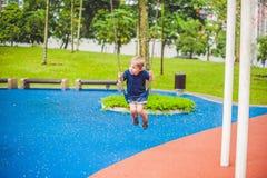 Reizender blonder kleiner Junge auf einem Schwingen im Park Entzückender Junge, der Spaß am Spielplatz hat Lizenzfreies Stockfoto
