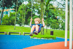 Reizender blonder kleiner Junge auf einem Schwingen im Park Entzückender Junge, der Spaß am Spielplatz hat Lizenzfreie Stockfotos