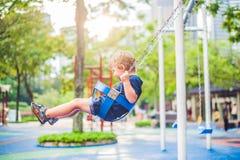 Reizender blonder kleiner Junge auf einem Schwingen im Park Entzückender Junge, der Spaß am Spielplatz hat Stockfoto