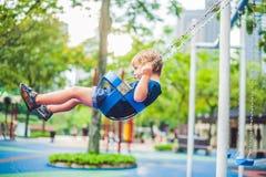 Reizender blonder kleiner Junge auf einem Schwingen im Park Entzückender Junge, der Spaß am Spielplatz hat Stockbilder