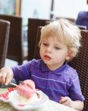 Reizender blonder kleiner Junge, der Eiscreme im Stadtcafé im Sommer isst Lizenzfreie Stockfotografie