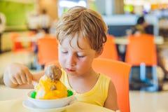Reizender blonder kleiner Junge, der Eiscreme im Stadtcafé im Sommer isst Lizenzfreie Stockfotos