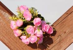 Reizender Blumenstrauß auf der hölzernen Beschaffenheit Lizenzfreie Stockfotos