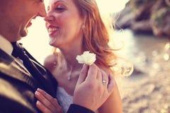 Reizender Bräutigam und Braut draußen an einem sonnigen Tag Lizenzfreie Stockfotos