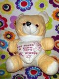 Reizender brauner Teddybär betreffen den nahtlosen Hintergrund, der oben für Karte Cerebration Schein ist stockfoto