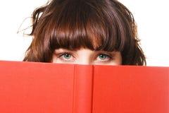 Reizender Brunette mit einem roten Buch Stockfotos