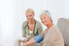 Reizender Doktor, der den Blutdruck nimmt Lizenzfreies Stockbild