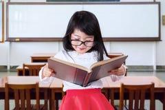 Reizender grundlegender Student, der ein Buch liest Lizenzfreie Stockfotografie