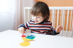 Reizender Junge, der mit geometrischen Zahlen spielt Lizenzfreie Stockfotografie