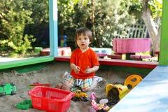 Reizender Junge, der mit Sand auf Spielplatz im Sommer spielt Stockfotografie