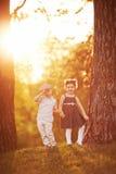 Reizender Junge und Mädchen auf Sonnenuntergang Lizenzfreies Stockfoto