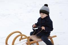 Reizender kleiner Junge auf altem Schlitten am Wintertag Stockbild
