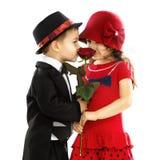 Reizender kleiner Junge, der dem Mädchen eine Rose gibt Stockbild
