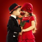 Reizender kleiner Junge, der dem Mädchen eine Rose gibt Lizenzfreies Stockbild