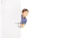 Reizender kleiner Junge, der einen flüchtigen Blick hinter einer Tür schleicht lizenzfreies stockfoto