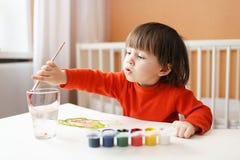 Reizender kleiner Junge mit Bürste und Farben zu Hause Stockbild
