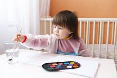 Reizender kleiner Junge mit Bürsten- und Wasserfarbe malt zu Hause Lizenzfreie Stockbilder