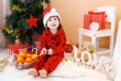 Reizender kleiner Junge in Sankt-Hut mit Lutscher und Geschenken sitzt n Stockbild