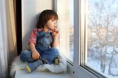 Reizender kleiner Junge sitzt auf Schwelle und schaut aus Fenster im Winter heraus Lizenzfreies Stockfoto