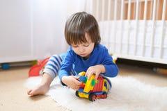 Reizender kleiner Junge spielt Autos zu Hause Lizenzfreie Stockfotografie