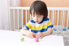 Reizender kleiner Junge stellte Zahnstocherbeine durch playdough Spinnen her Stockfoto