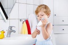 Reizender Kleinkindjunge, der seine Zähne, zuhause putzt Lizenzfreie Stockbilder