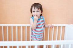 Reizender Kleinkindjunge im weißen Bett Stockbilder