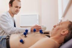 Reizender mitfühlender Doktor, der seinen Patienten beruhigt stockfoto