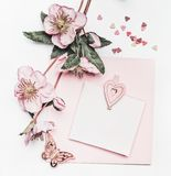 Reizender Pastellrosaplan mit Blumendekoration, Band, Herzen und Kartenspott oben auf weißem Schreibtischhintergrund, Draufsicht, lizenzfreies stockbild