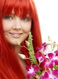 Reizender Redhead mit Orchidee Stockfotos