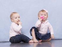 Reizender Säuglingsjunge und lustiges Baby, die auf dem Boden sitzt und Kameramann betrachtet Lizenzfreies Stockfoto